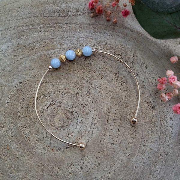 Bracelet jonc gold filled or jaune avec pierre morganite bleu pastel vue sur bois