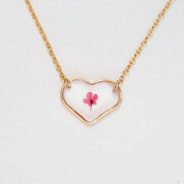 Collier avec médaillon cœur et contenant une fleur d'ammi majus rouge vue de près