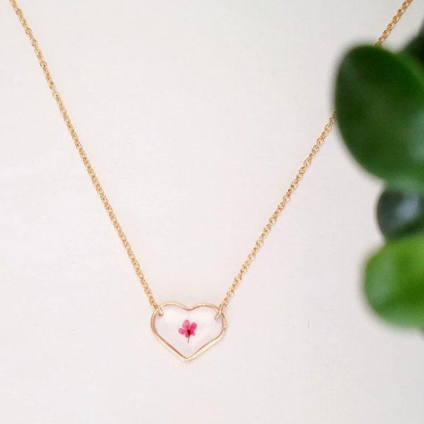 Collier avec médaillon cœur et contenant une fleur d'ammi majus rouge vue d'ensemble